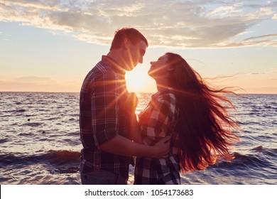 couple in love back light silhouette at lake orange sunset