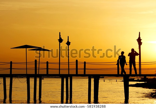 couple in love back light silhouette at sea sunset