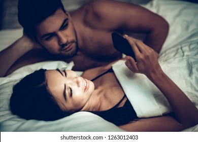 Couple in Love in Bed, Girl Using Mobile Phone. Spending Time with Each Other. Woman and Man Lying on Bed in Bedroom. Girlfriend and Boyfriend. Internet Conctent. Texting Message. Love Concept.