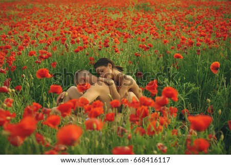 Couple in love - Beginning of a Love Story.  Portrait of a beautiful elegant couple in love, kissing in the park, romantic date. Stylish man and woman. Sexy couple. Red flowers background. Erotica
