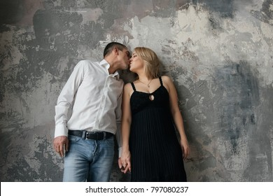 Couple in love. A blonde girl in a black dress, a guy in a white shirt and jeans. Room in loft style. Stand near the texture wall. They hold on to the hand.