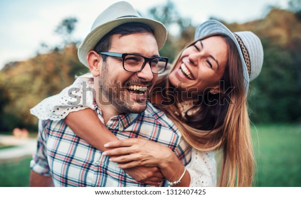 Couple in love. Boyfriend carrying his girlfriend on piggyback. Love and tenderness, dating, romance. Lifestyle concept