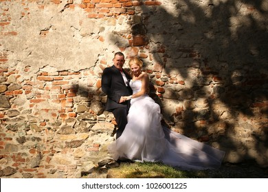couple in love, the bride and groom standing near a old brick wall