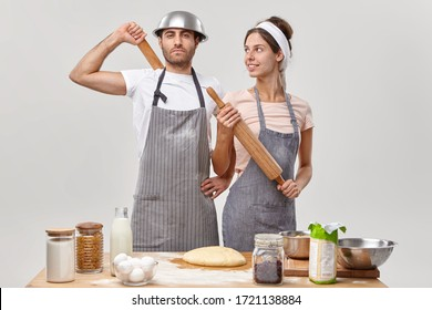 Couple in love busy with family cooking, stand self assured at kitchen, make dough for preparing pie, have all needed ingredients, hold rolling pin, prepare for party. Food, cooking, recipe concept