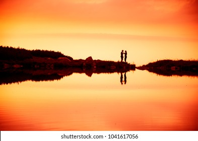 couple in love by lake in mountains. silhouette sunset sky