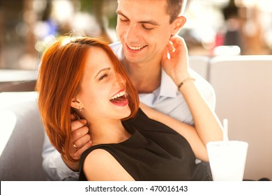 couple in love in a cafe laughing and hugging