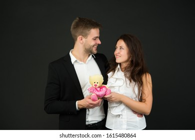 Couple in love celebrate valentines day. Surprise. Flirting and dating. Love and romance. Gift with love. Couple on romantic date. Formal couple with toy. Man and woman corporate attire fashion.