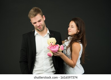 Couple in love celebrate valentines day. Surprise. Unacceptable initiative. Love and romance. Gift with love. Couple on romantic date. Formal couple with toy. Man and woman corporate attire fashion.