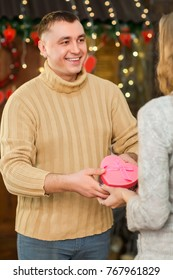 couple in love celebrate valentine's day. handsome man giving present in pink box to his pretty woman