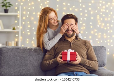 Couple in love celebrating special date. Smiling woman covering boyfriend eyes giving him surprise gift. Happy young man getting Saint Valentines Day, Christmas or birthday present from girlfriend