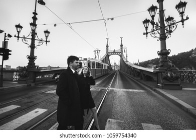 Couple in love is crossing the liberty bridge over the river Danube in Budapest. Man and woman in urban city. Vintage tram on bridge in Europe. Black and white stylish fashion photo in movement.