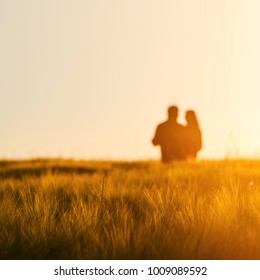 Couple in love dancing together in gold wheat field