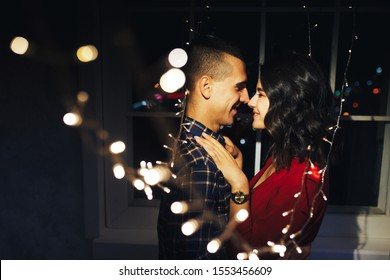 couple in love in the dark between the lights of garlands hugs and kisses.holiday and date for christmas. twelve hours, kiss on new year's eve. in the lights on the background of the window.