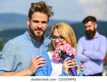 Couple in love dating while jealous bearded man watching wife cheating him with lover. Infidelity concept. Lovers hugs outdoor flirt romance relations. Couple romantic date lovers bouquet flowers.