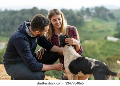 couple in love with a dog in the mountains