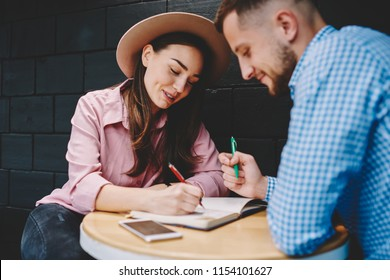 Couple in love dressed in casual wear discussing plan of common rest and writing down checklist in notepad spending leisure time in modern coffee shop.Young marriage noting list to do in notebook