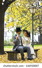 A couple in love, dressed in the style in the end of the 19th century, sitting on a park bench in fall.