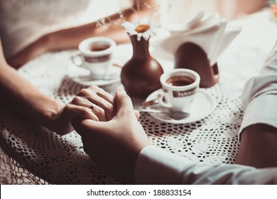 Couple in love drink coffee in cafe, holding each other's hand. Photo is processed in coffee color tone. Concept of male and female hands, love and coffee. Focused on hands.
