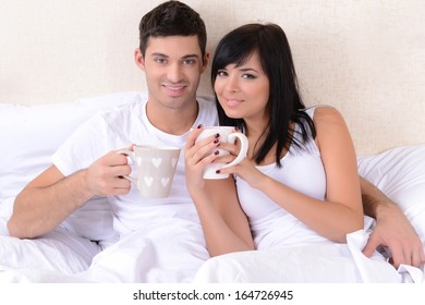 Couple in love drinking coffee in bed
