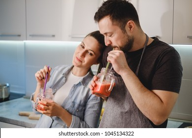 Couple in love drinking smoothie from the jar with a straw in the kitchen