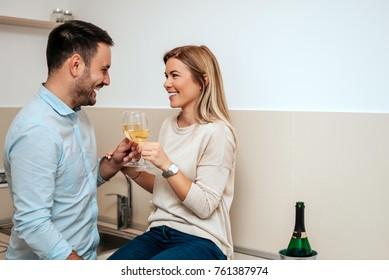 Couple in love drinking wine in their kitchen.