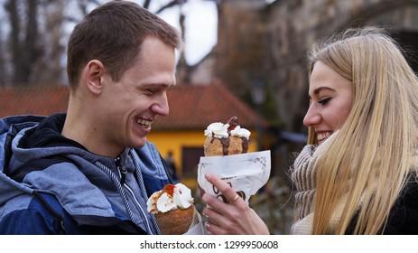 Couple in love eat Trdelnik in Prague