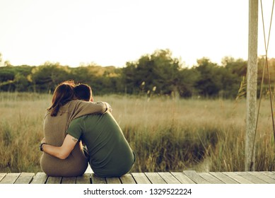 Couple in love embraced on their backs to reconcile and celebrate their love, sitting in nature.