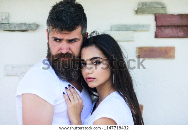 Couple in love enjoy each other romantic date. Man bearded and girl hugs or cuddling. So good to feel your hug. Tender hug. Couple in love romantic date cuddling outdoors light wall background.