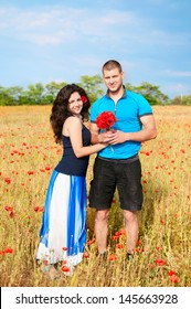 couple in love enjoy a moment of happiness in blossom spring garden with field flowers on nature. handsome young man and beautiful brunette girl happy. Loving couple on date in park looking happy