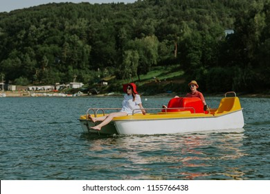 Couple in love enjoying boating in the lake. Portrait of young man and woman pedal boating on the river.