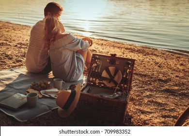 Couple in love enjoying picnic day next to the river.
