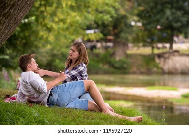 Couple in love enjoying picnic time drink and food in beautiful nature on the river bank