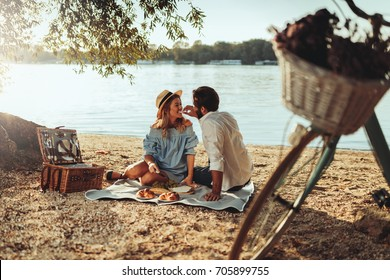 Couple in love enjoying picnic time and food outdoors.