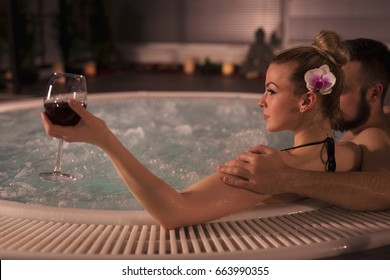 Couple in love enjoying the romantic atmosphere of a jacuzzi bath, drinking wine and relaxing