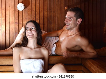 couple in love enjoying the sauna with white towels. The pleasure of a good spa session