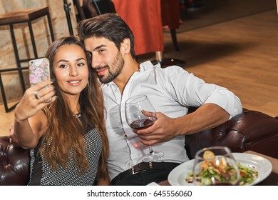 Couple in love enjoying time in a restaurant and taking selfie