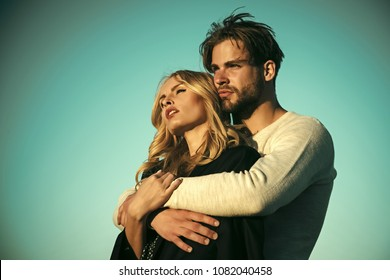 Couple in love. Family couple of man and sexy girl, trust. Muscular man and woman with long blond hair, love. Relations of happy family, future. Couple in love on blue sky background. Love and romance