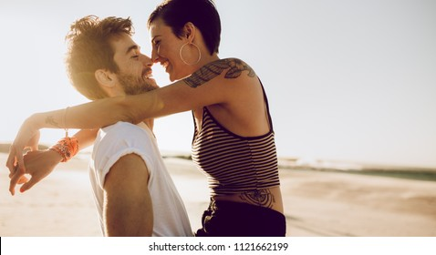 Couple in love flirting outdoors. Young man and woman in holiday. Boyfriend carrying his girlfriend and smiling.