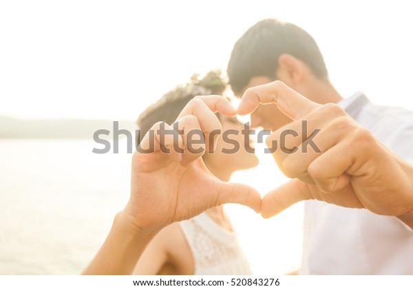 Couple in love gesturing heart with fingers against sunrise