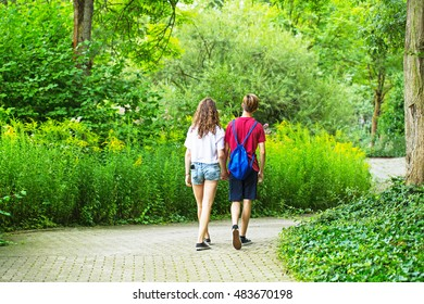couple in love girl and boy teens holding hands walking through the Park on wide road