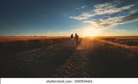A couple in love go hand in hand to meet the sunset. Silhouette of a guy with a guitar that leads by the hand of a girl. Newlyweds in country style. View from the back.