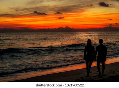 Couple in love hand in hand watching sunset at the ocean