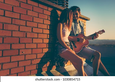 Couple in love hanging out at a rooftop party, leaning against a brick wall ; guy playing the guitar and singing