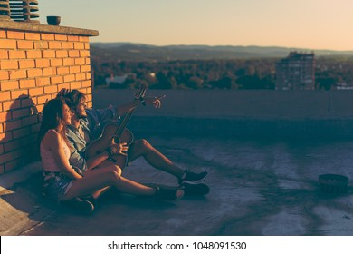 Couple in love hanging out at a rooftop party, sitting on the floor, leaning against a brick wall and enjoying a beautiful summer sunset