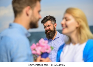 Couple in love happy dating, jealous bearded man watching wife cheating him with lover. Lovers meeting outdoor flirt romance relations. Jealous concept. Couple romantic date lovers bouquet flowers.