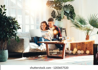 Couple in love. Happy family watching TV series using laptop and sitting on the couch