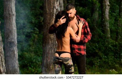 Couple in love have sex outdoor, trees on background, defocused. Love and sex concept. Man and woman undressing, nude woman in black lingerie. Erotic couple full of desire going make love.