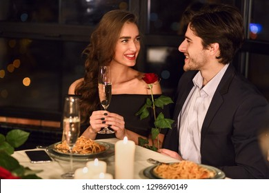 Couple in love having dinner in restaurant, woman drinking champagne, man holding rose smiling and talking