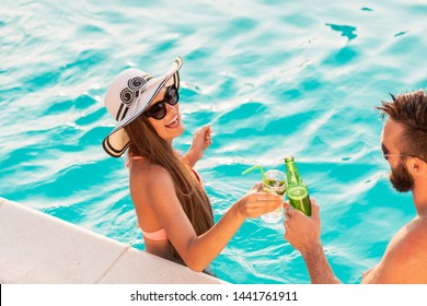 Couple in love having fun at a poolside summer party, standing in water next to the swimming pool edge, making a toast