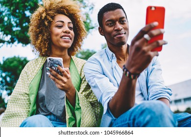 Couple in love having fun reading news and posts in social networks spending time on date in city park,dark-skinned friend choosing photo for update profile picture viewing images on smartphone